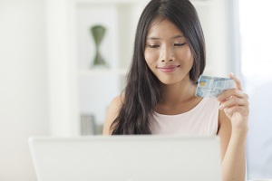 Smiling Asian woman shopping online with her credit card.